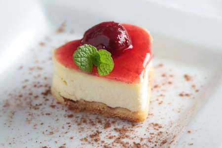 Heart-shaped slice of cheesecake with cherry jam Stock Photo - 12895349