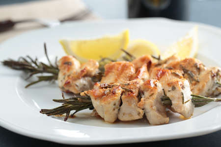 Chicken souvlaki on rosemary branches with lemon photo