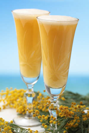 Two glasses of mimosa cocktail against bunch of flowers photo