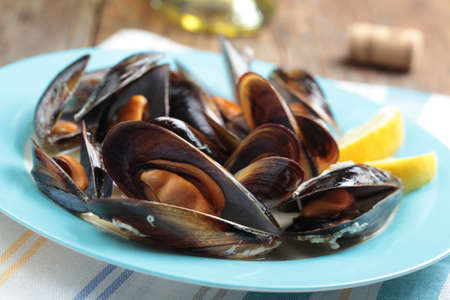 Roasted mussels with lemon on a plate photo