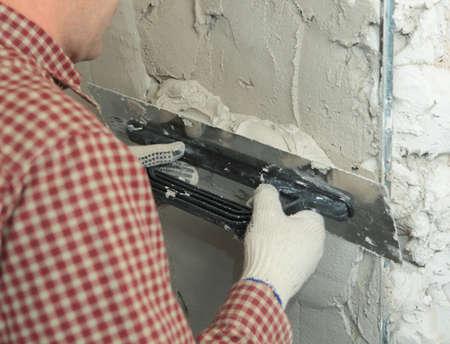 Worker stukadoors een muur met behulp van troffel