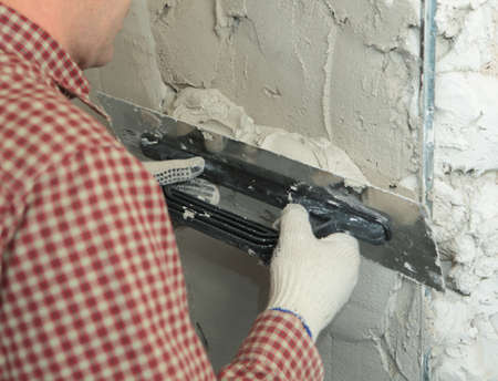 Worker plastering a wall using trowel