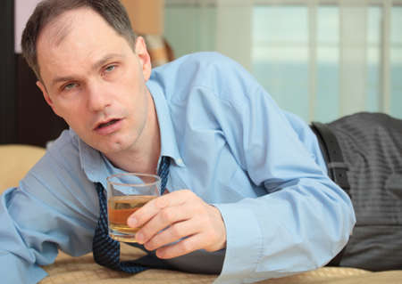 Drunk businessman on a bed in hotel room holding a glass of whisky Stock Photo - 13032264
