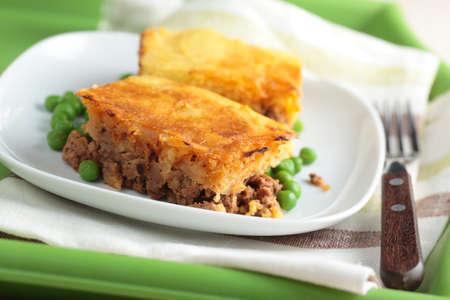 Cottage pie on a plate with green peas