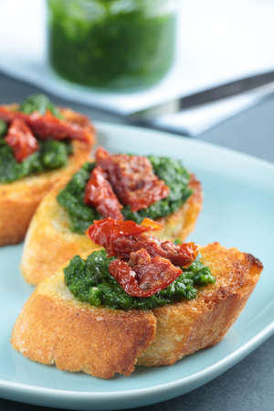 Crostini with pesto sauce and sun-dried tomatoes photo