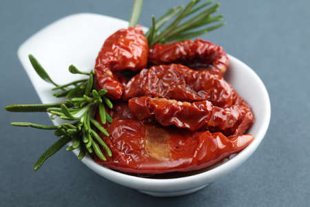 Zongedroogde tomaten en rozemarijn in een kleine kom
