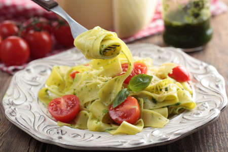Pasta with pesto sauce, cherry tomato, basil, and cheese photo