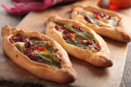 Turkish pides with vegetables on a wooden cutting board