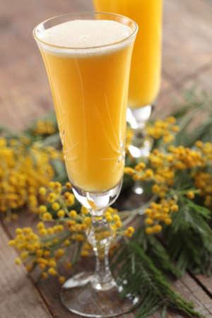 Two glasses of mimosa cocktail against bunch of flowers