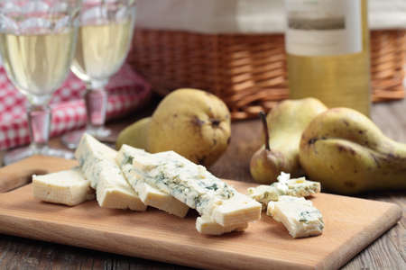 Sliced blue cheese, pears, and white wine on a rustic table photo