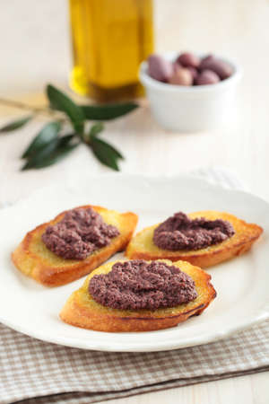 Crostinis with olive pate on a rustic table photo