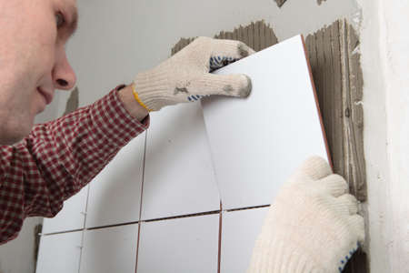 Contractor installing tiles on a wall Imagens