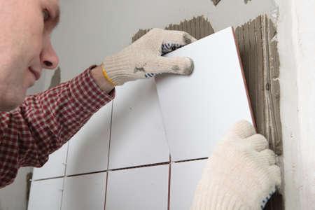 Opdrachtnemer het installeren van tegels op een muur Stockfoto