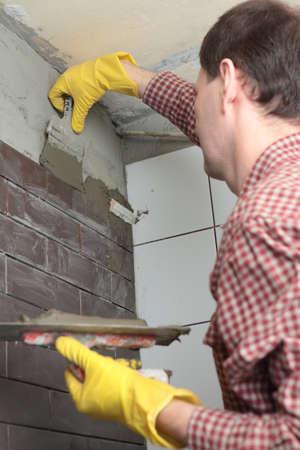 clinker: Contraente l'installazione di piastrelle su una parete Archivio Fotografico