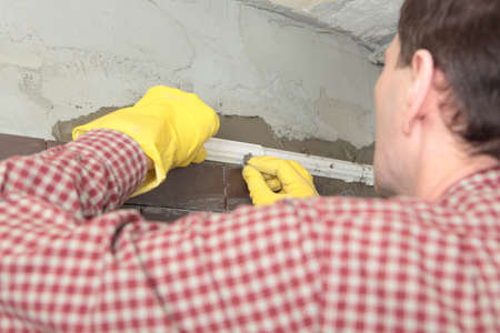 clinker tile: Contractor installing tiles on a wall Stock Photo