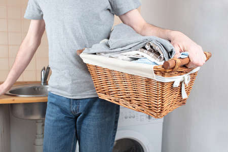 Man holding a basket with clothes against washing machine Stock Photo - 13033894