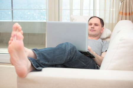 Man with laptop lying on a sofa photo