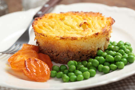 Cottage pie on a plate with carrot and green peas photo