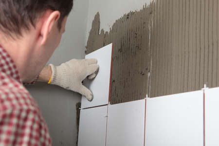 Contractor installing tiles on a wall photo