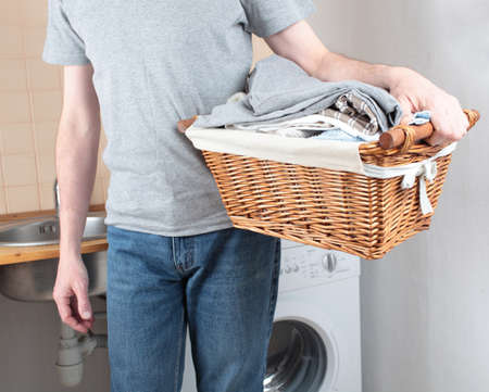 Man holding a basket with clothes against washing machine photo