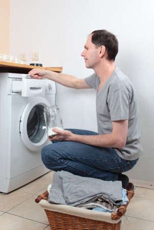 Man loading detergent into washing machine photo