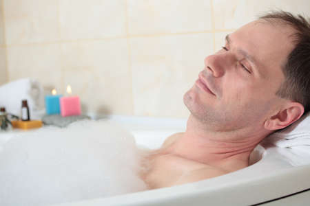 Adult man having a bath with essential oil