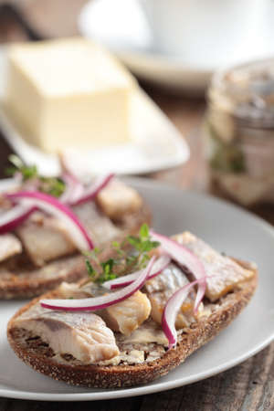Sandwich with butter, herring, red onion, and thyme photo