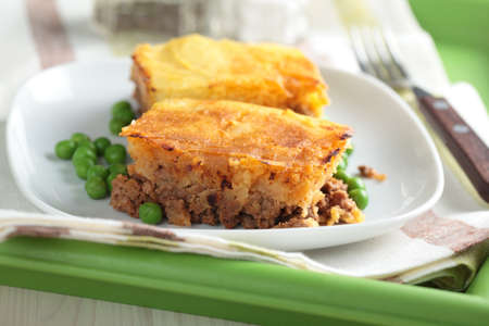 Cottage pie on a plate with green peas photo