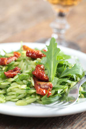 Salad with orzo pasta, rocket, pesto sauce, and sun-dried tomatoes photo