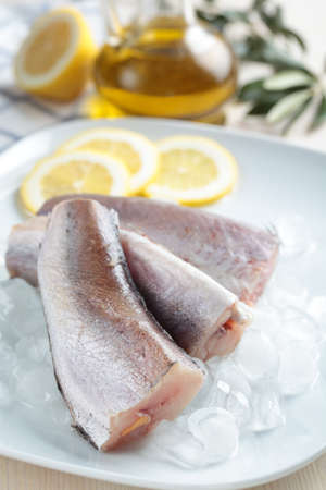 hake: Raw hake on ice and slices of lemon