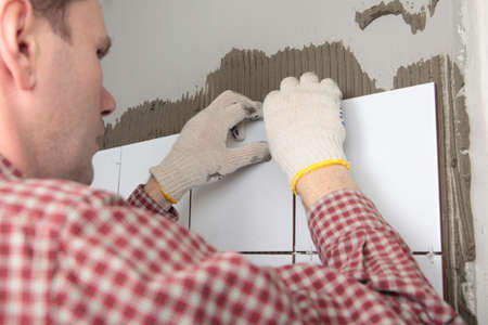 Contractor installing tiles on a wall Stock Photo - 13761925