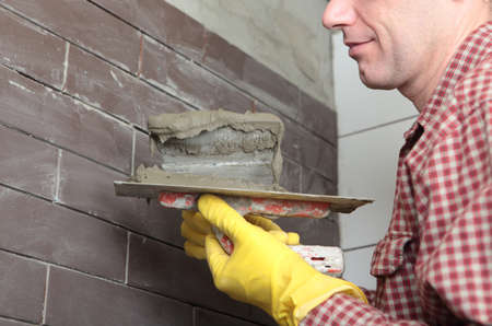 clinker: Contractor installing tiles on a wall Stock Photo