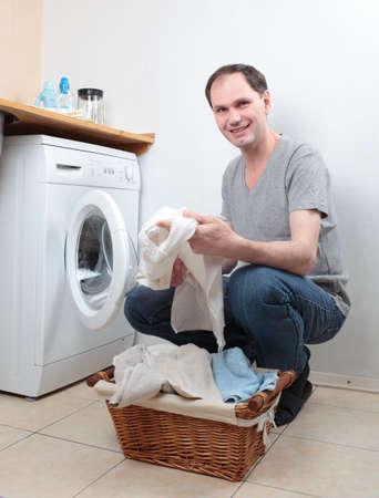 Man loading clothes into washing machine Stock Photo - 13761763