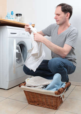 Man loading clothes into washing machine photo