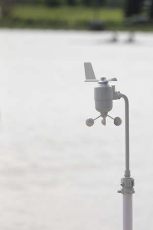 anemometer: Anemometer and vane on a stand against a rowing stadium