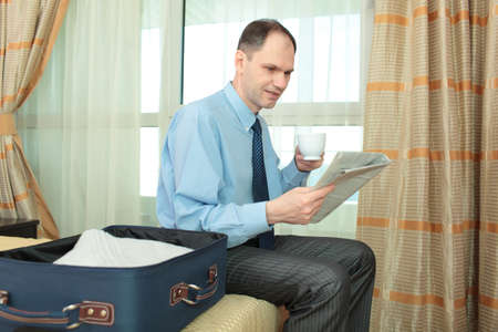 Businessman reading newspaper in a hotel room photo