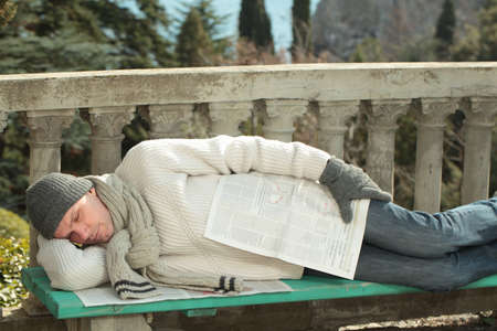 Man sleeping on a bench under newspaper photo