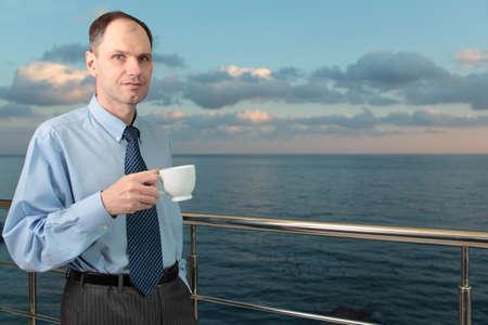 Businessman drinking coffee on a balcony against a sea photo