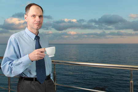 Businessman drinking coffee on a balcony against a sea photo