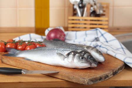 Raw sea bass on a wooden cutting board photo