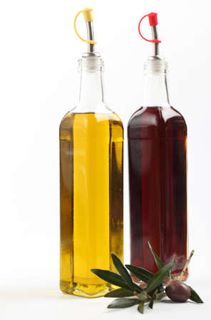 Olive branch with fruit against bottles with olive oil and vinegar photo