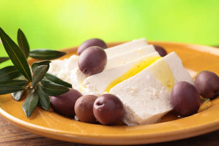 Feta cheese with calamata olives, olive oil, and olive branch photo