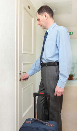 Businessman with keys opening the door of his hotel room Stock Photo