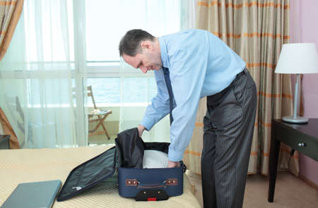 Businessman putting sweater into a suitcase photo