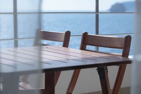 Table and folded chairs on a balcony against a sea photo