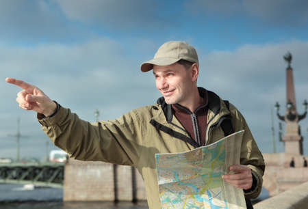 neva: Tourist with a map pointing away on a quay of Neva river in St. Petersburg, Russia