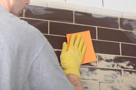renovation: Contractor grouting ceramic tiles on a wall