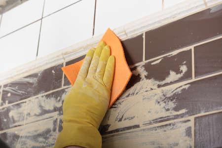 Opdrachtnemer voegen keramische tegels op een muur