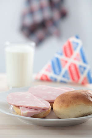 Sandwich with Bologna sausage and a pack with milk on a kitchen table photo