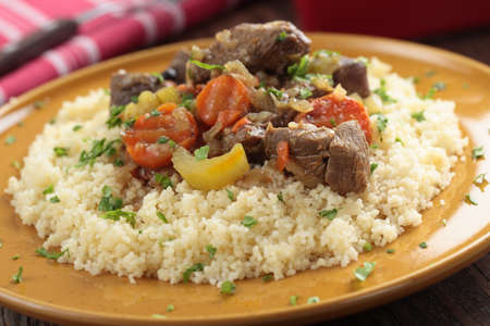 Lamb meat with vegetables and couscous on a plate photo